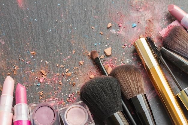 Set borstels, lippenstiften en oogschaduw met kopie ruimte op zwarte achtergrond