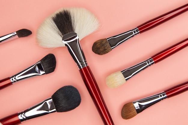 Set borstels voor het aanbrengen van cosmetica op een roze tafel