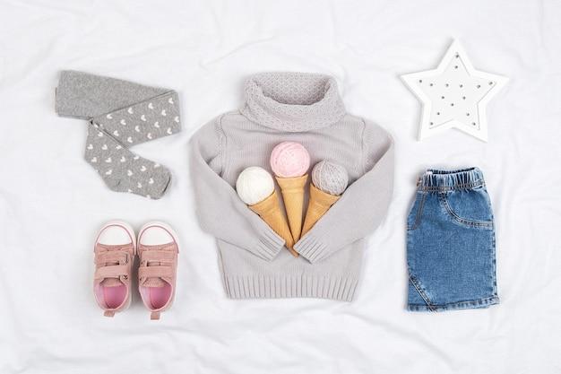 Set casual kinderkleding, schoenen en accessoires op witte achtergrond. mode meisje lookbook concept. gebreide trui, spijkerrok, sneakers, ijshoorntje. bovenaanzicht, plat gelegd.