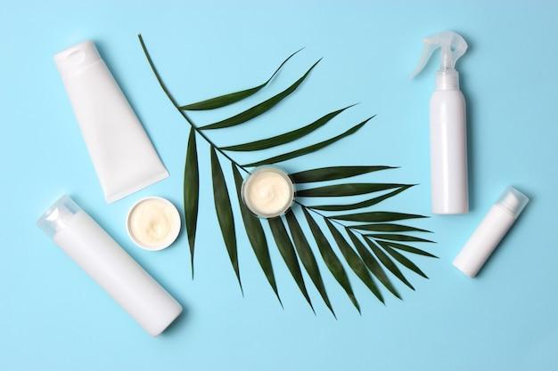 Set cosmetische potten van witte kleur en palmtakken op een gekleurde achtergrond bovenaanzicht close-up. hoge kwaliteit foto