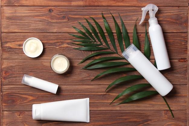 Set cosmetische potten van witte kleur en palmtakken op een gekleurde achtergrond