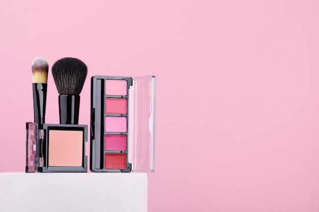 Set cosmetische producten lippenstiften, poeder, make-up kwasten op roze achtergrond. schoonheidsproducten voor professionele modieuze make-up door een visagist. damesaccessoires voor huidverzorging. ruimte kopiëren.