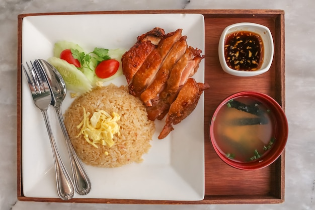 Set gebakken rijst knoflook met gegrilde kip teriyaki en soep met lepel en vork in de houten lade op het witte stenen graniet