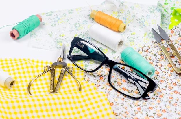 Set gele en groene stoffen, schaar, knopen, klosjes draad en glazen op geel