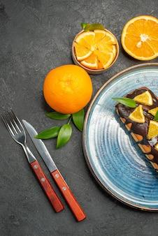 Set gele hele en gesneden citroenen smakelijke taarten met mes en vork op donkere tafel