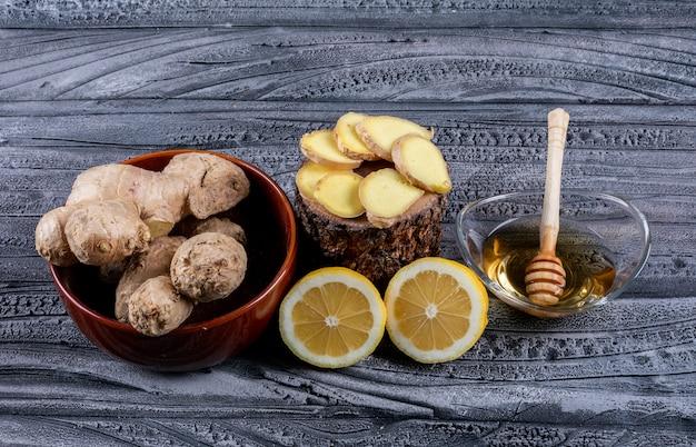 Set gember segmenten, citroen en gember en honing in een kommen op een donkere houten achtergrond. bovenaanzicht.