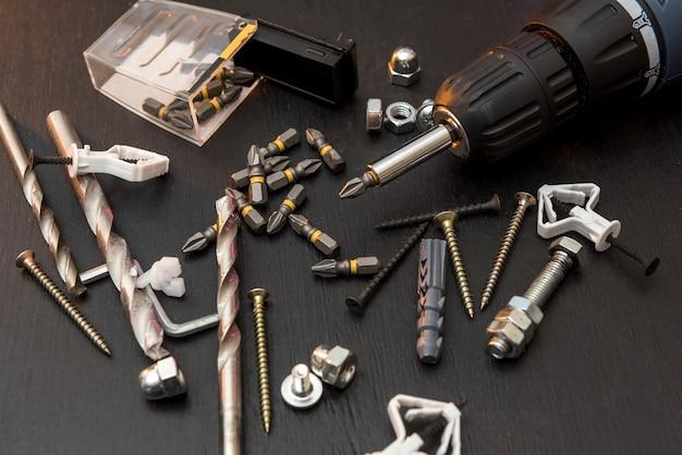 Set gereedschap op tafel, een schroevendraaier met een set boren en schroeven met bouten. allemaal voor reparatie