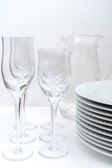 Set gestapelde witte borden, kristallen glaswerk en een glazen kan op een witte tafel.