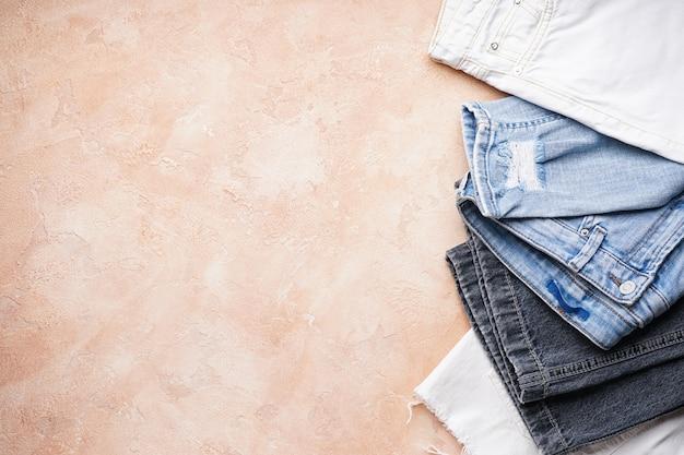 Set gevouwen jeans op een beige, ruimte voor tekst, bovenaanzicht.
