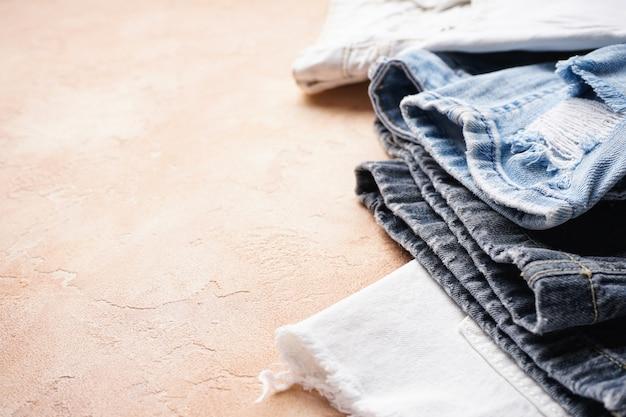 Set gevouwen jeans op een beige, ruimte voor tekst. detailopname