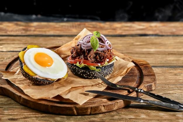 Set hamburger met ei en bier. een standaard set drankjes en eten in de kroeg, bier en snacks. donkere achtergrond, fastfood. traditioneel amerikaans eten.