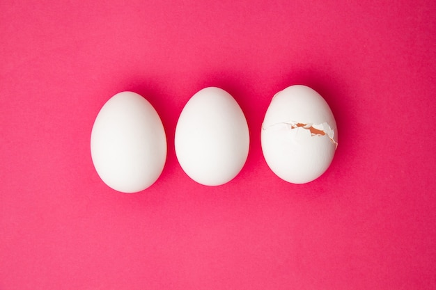 Set hele en gebarsten eieren op roze oppervlak