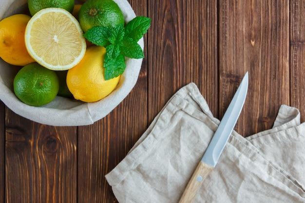 Set houten mes, halve citroen en citroenen in een mand op een houten tafel. bovenaanzicht.