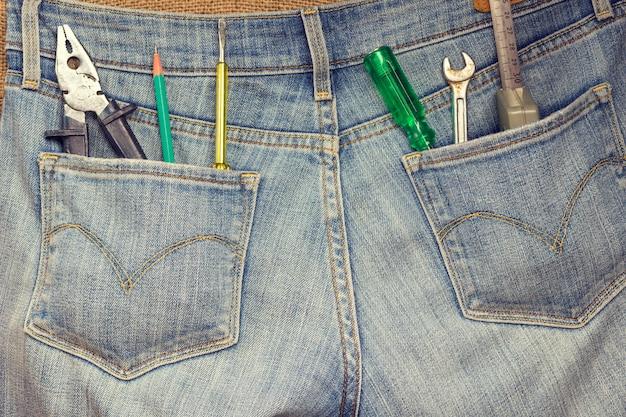 Set huisgereedschap voor reparatiewerkzaamheden in jeanszakken.