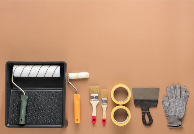 Set hulpmiddelen om te schilderen. rollers, borstels, plakband, spatels en handschoenen. reparatieproces.