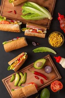 Set ingrediënten voor sandwiches met ham op een donkere tafel, bovenaanzicht.