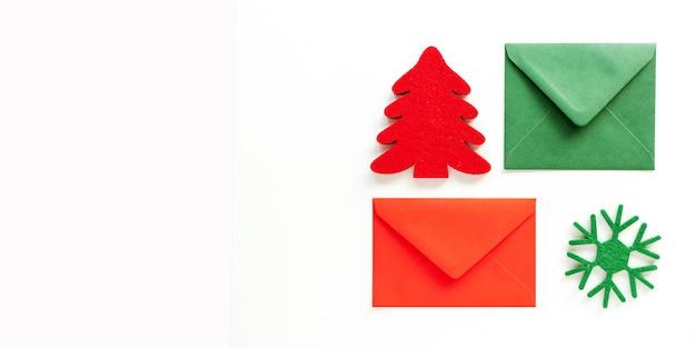 Set kerst enveloppen en vilten decoratie op wit. bannerontwerp, bovenaanzicht, plat leggen, kopie ruimte.