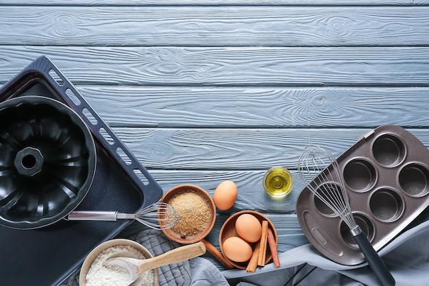 Set keukengerei en ingrediënten voor het bereiden van bakkerij op donkere houten achtergrond