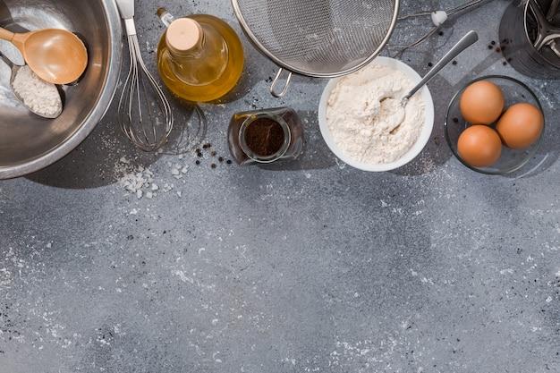 Set keukengerei met producten op grijs-blauwe achtergrond. masterclasses koken. kopieer ruimte.