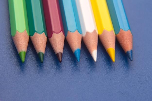 Set kleurpotloden op een blauwe achtergrond. teken hulpmiddelen. palet in creativiteit