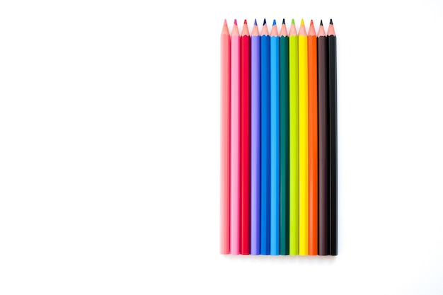 Set kleurpotloden van alle kleuren van de regenboog liggen verticaal op een rij op een witte achtergrond