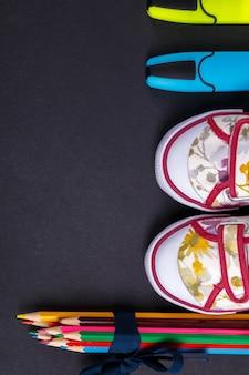 Set kleurpotloden verpakt in een blauw lint in de buurt van sneakers en marker op zwarte houten achtergrond. terug naar school.