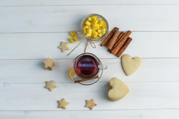 Set koekjes, citroen, kaneelstokjes, suikerklontjes en thee in een glazen beker op een houten achtergrond. bovenaanzicht.