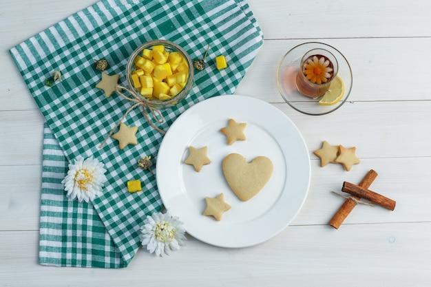 Set koekjes, kaneelstokjes, suikerklontjes, bloemen en thee in een glas op houten en keukenhanddoekachtergrond. bovenaanzicht.