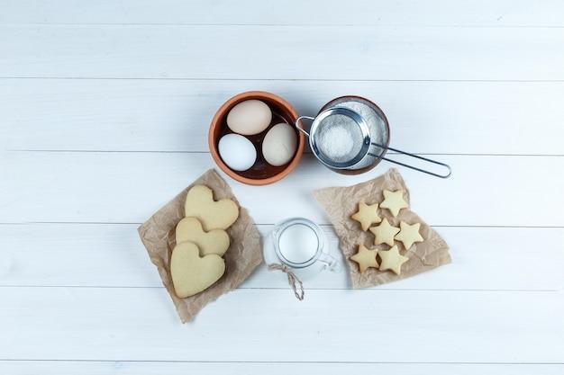 Set koekjes, melk, suikerpoeder en eieren in een kom op een houten achtergrond. bovenaanzicht.