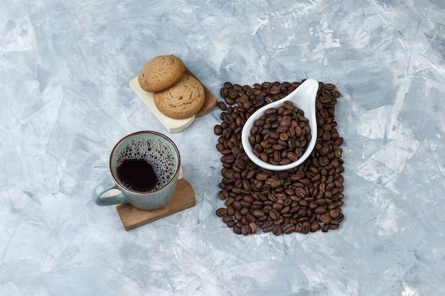 Set koekjes op een snijplank, kopje koffie en koffiebonen in een witte porseleinen kruik