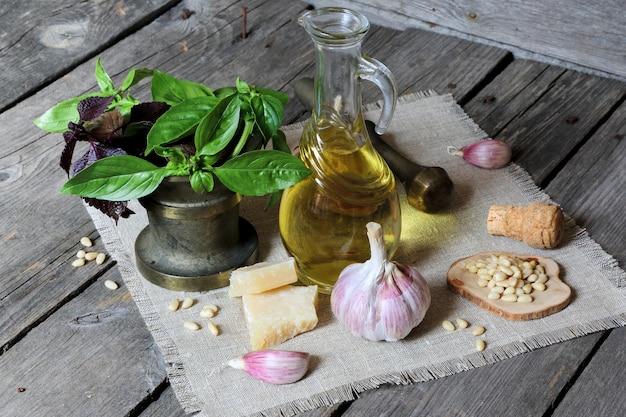 Set kruiden, specerijen en andere producten voor de bereiding van italiaanse pestosaus op een donkere houten ondergrond