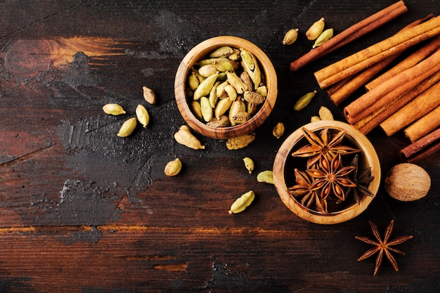 Set kruiden van steranijs, kardemom, kaneel en bruine suiker op oude houten achtergrond. plat leggen.