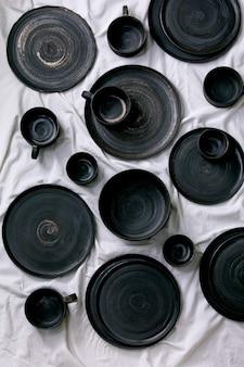 Set lege zwarte handgemaakte keramische borden, kommen en kopjes op wit linnen tafelkleed als achtergrond. plat leggen.