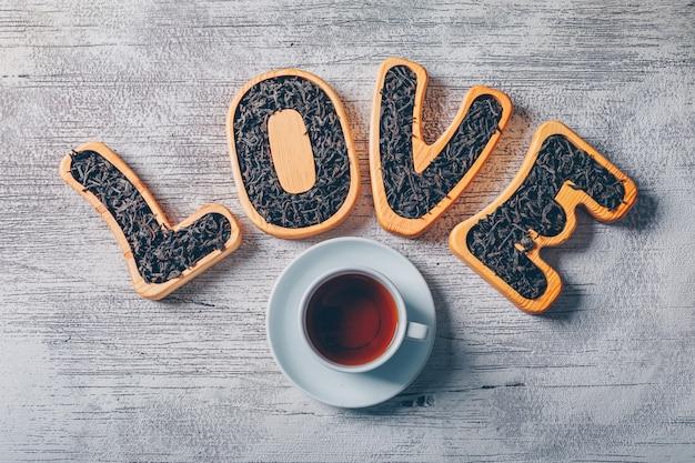 Set liefde tekst gevuld met thee en een kopje thee op een witte houten achtergrond. bovenaanzicht.