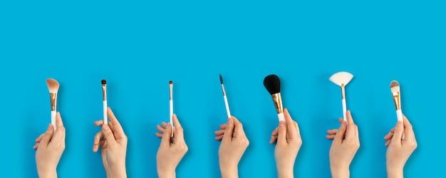 Set make-up borstels in vrouwelijke hand op de achtergrond van oogschaduw sets.
