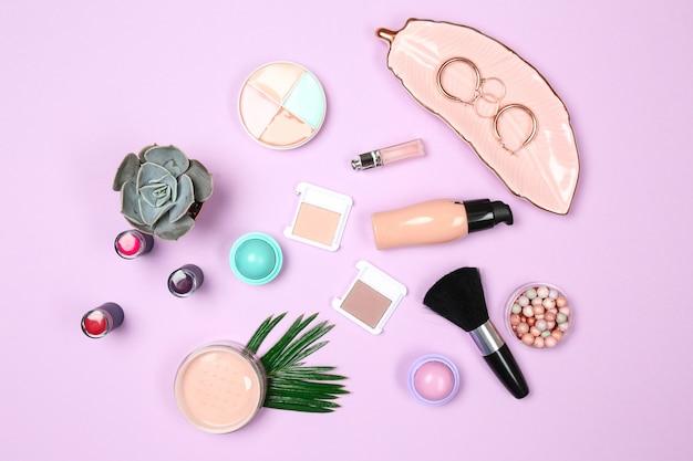 Set make-up cosmetica met sieraden op kleur oppervlak