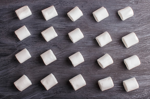 Set marshmallows op zwarte houten achtergrond. geometrisch patroon.