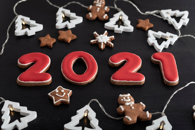 Set met nummers 2021 van gemberkoekjes geglazuurd suikerglazuur. sneeuwvlokken, sterren, peperkoekmannetje en slinger.