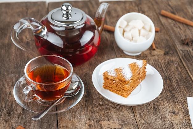 Set met theepot, kopje en een plakje honingkoek op de houten tafel