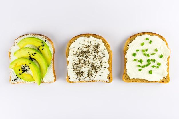 Set met toastbrood en verschillende toppings met superfoods, chiazaadjes, sesamzaadjes op wit, bovenaanzicht.