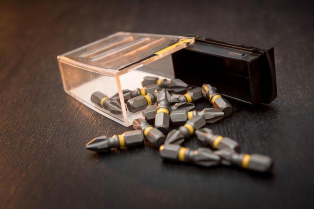 Set metalen bits verspreid over een zwarte tafel schroevendraaier. allemaal voor reparatie
