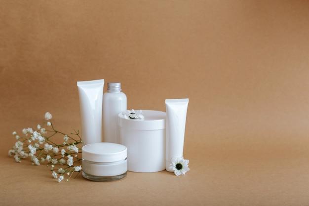 Set natuurlijke schoonheid cosmetische huidverzorgingsproducten met bloemen zeeschelpen op beige achtergrond met kopieerruimte. witte kit zalfpotje buis cosmetische producten voor lichaamsbehandeling huidverzorging cosmetische mockup.