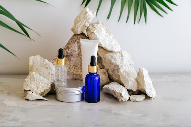 Set natuurlijke schoonheid cosmetische huidverzorgingsproducten met palmblad plant op stenen sokkel, rots stapel balanceren stenen grijze achtergrond. serum druppelaar crème boter lichaamsverzorging cosmetische mockup.