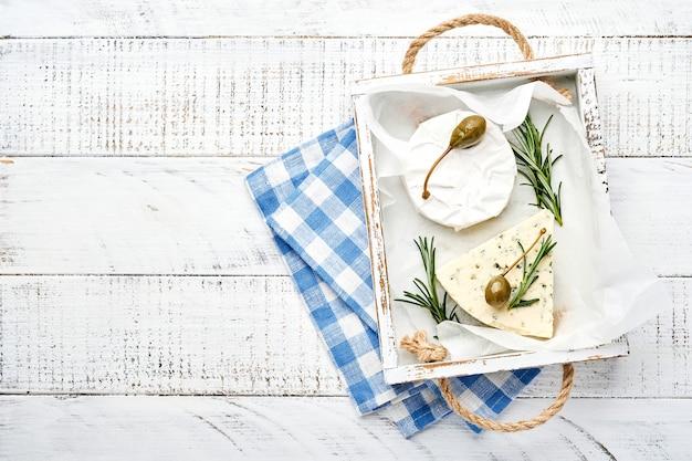 Set of assortiment kazen. camembert, blauwe kaas en brie met rozemarijn, kappertjes en peper.