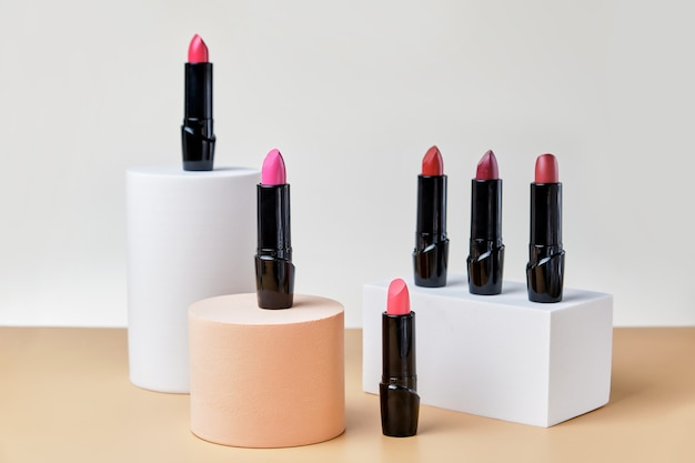 Set open lippenstiften op trendy sokkels, een merkloze presentatie van cosmetica op een lichtbeige ondergrond