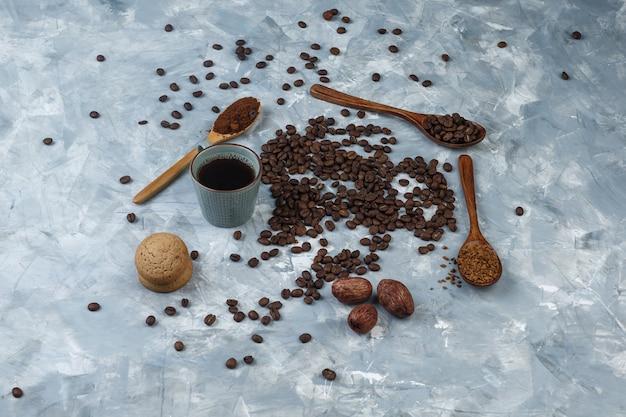 Set oploskoffie, koffiemeel, koffiebonen in houten lepels, koekjes en koffiebonen, kopje koffie op een lichtblauwe marmeren achtergrond. hoge kijkhoek.