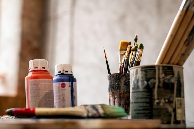 Set penselen in blikken en twee plastic potjes met rode en blauwe gouache op werkplaats van schilder