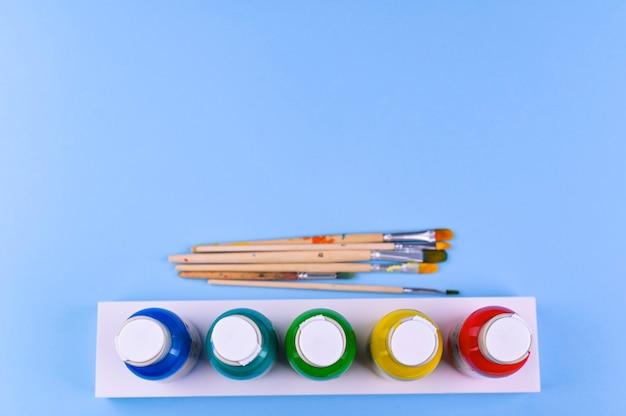 Set platte kunstenaar penselen met getekende tips op blauwe achtergrond en blikjes verf