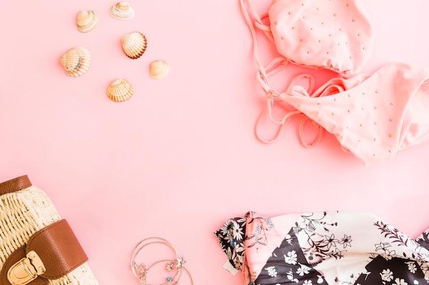 Set schelpen en strandvakantie accessoires op roze achtergrond