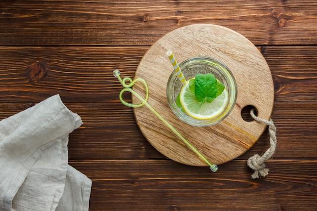Set snijplank, stro, witte doek en gesneden citroen in een kom op een houten oppervlak. bovenaanzicht.